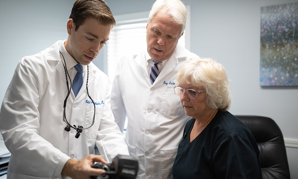 Dr. Cole and Dr. Gary showing a patient a picture on a camera