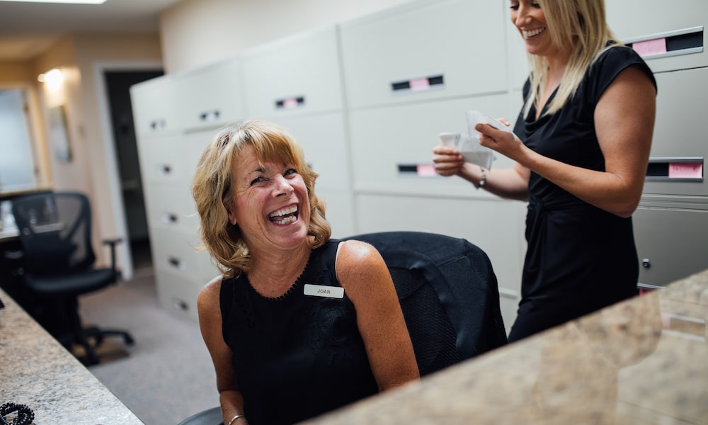 Two front of house team laughing behind the reception desk