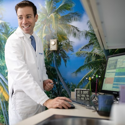 Dr. Cole Archambault standing in front a computer looking over his shoulder and smiling