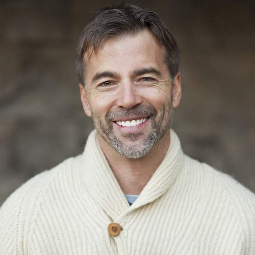 Man with short brown hair and wearing a cream top while smiling