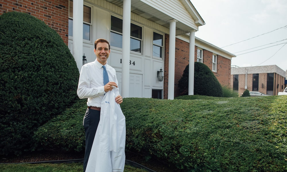 Dr. Cole Archambault, D.M.D standing in front of the Elm Family Dentistry building