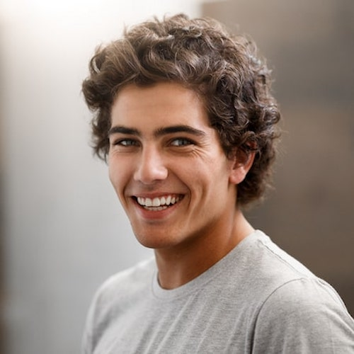 Young man with curly brown hair smiling while wearing a t-shirt