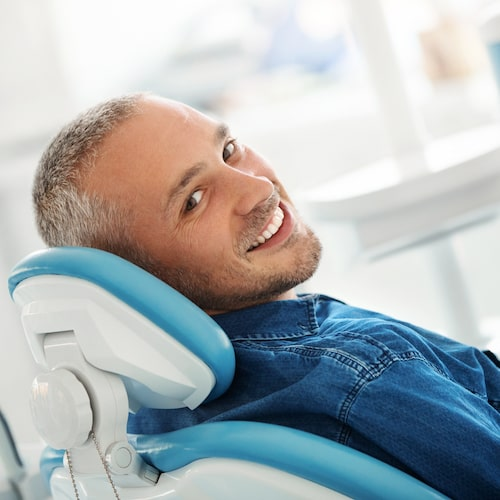 Man with short greying hair sitting in dental chair and looking back while smiling