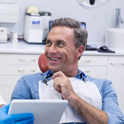 Man sitting in dental chair looking to his left and smiling while the assistant shows him something on the tablet