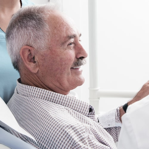 Older man with a moustache sitting in a treatment chair wearing a chequered shirt