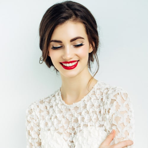 Beautiful woman wearing white and looking down while she smiles