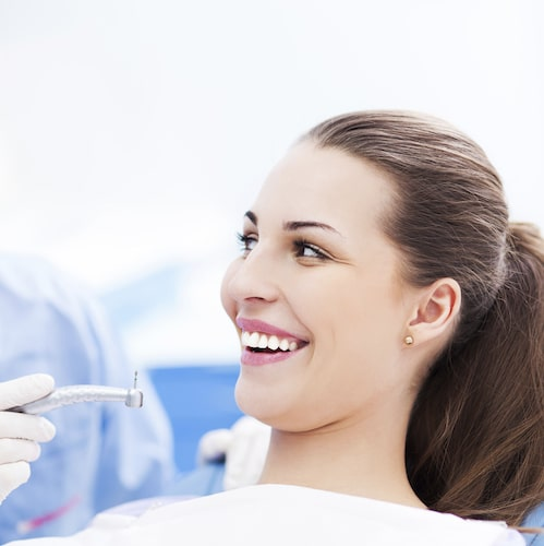 Woman sitting in dental chair with brown hair tied back and smiling at a dentist