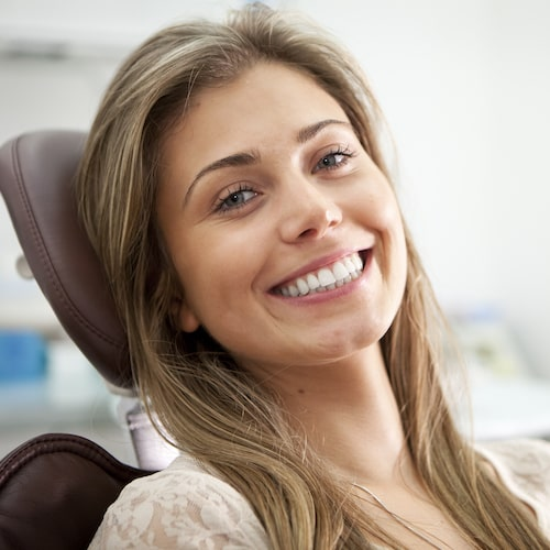 Young woman sitting in a dental chair with long light-brown hair and smiling