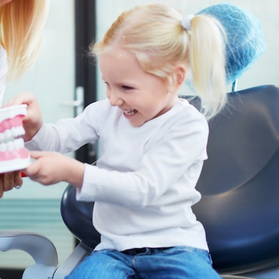 Young girl sitting in chair playing with a set of giant fake teeth