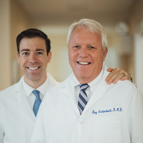 Dr. Cole with his arm around Dr. Gary while they both smile
