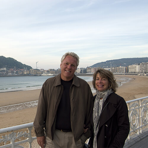 Dr. Gary Archambault, D.M.D and his wife standing side by side in front of a beach